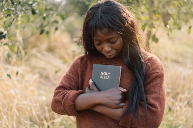 Христианская афро-девушка держит в руках библию