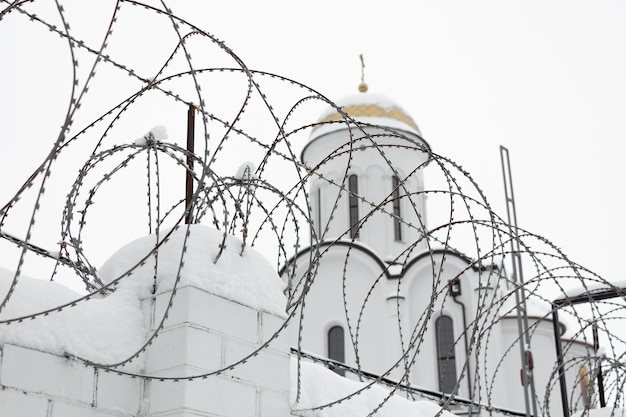 Christian church behind a fence with barbed wire in winter.