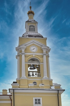 Христианская церковь с колокольней и башней с часами на фоне голубого неба