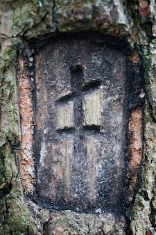 기독교 신조. 나무에 새겨진 십자가. 수직 프레임