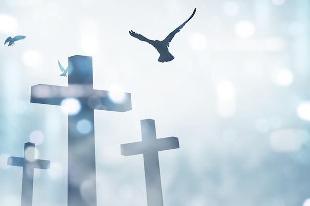 기독교 십자가와 흐린 빛을 배경으로 비행 비둘기