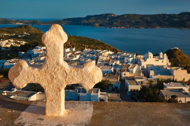 ギリシャの日没の赤いゼラニウムの花の上のミロス島のキリスト教の十字架とプラカ村