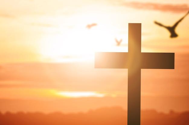 キリスト教の十字架と日の出の空を背景に鳩のシルエット