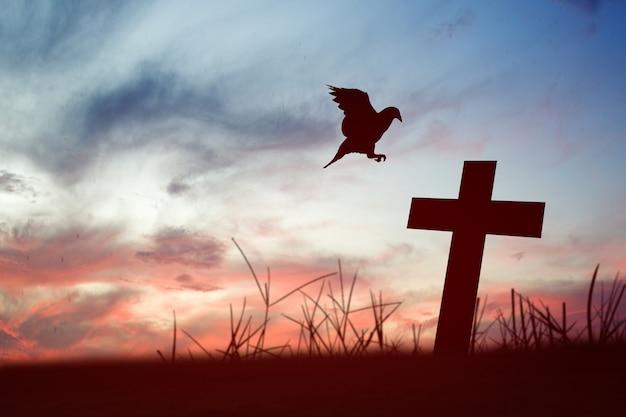 기독교 십자가와 일출 하늘 배경으로 비둘기의 실루엣