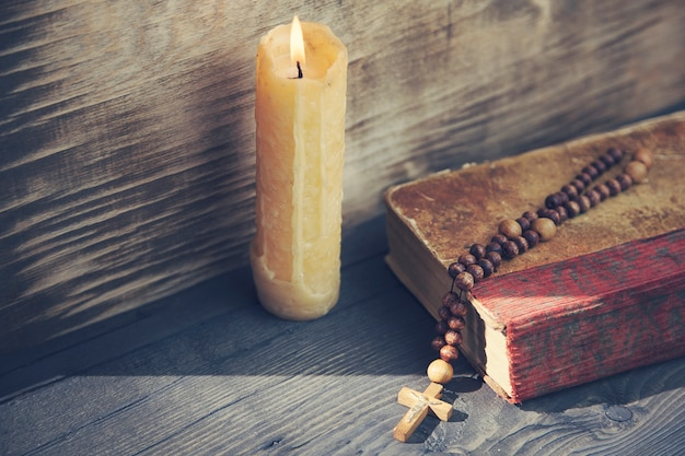Christian cross, candle and book on the wooden table