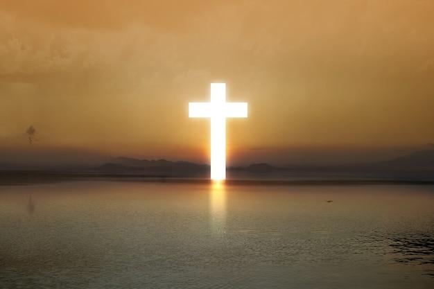 日の出の空を背景に湖の端にあるキリスト教の十字架