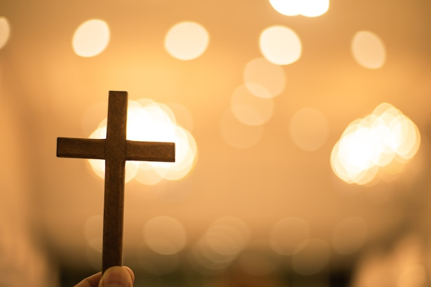 Christian cross with blurred bokeh background light at church.