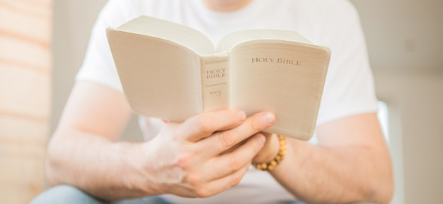 The christian holds the bible in his hands. reading the bible. the concept of faith, spirituality and religion