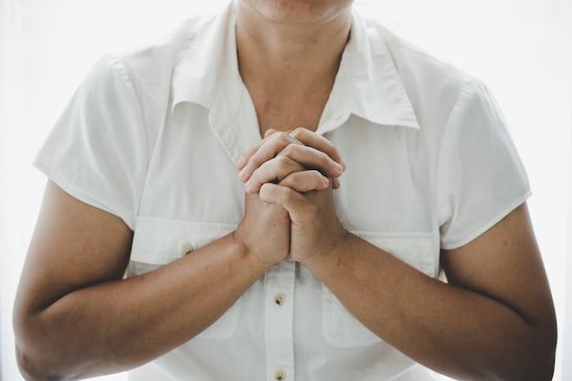 神へのキリスト教の生命危機の祈り。女性は、より良い生活を送りたいという神の祝福を祈ります。聖書で神に祈る女性の手。許しを乞い、善を信じます。