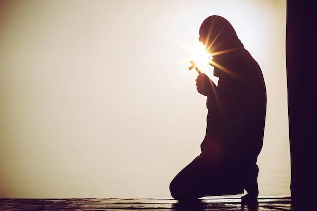 극적인 하늘 배경으로 예수 그리스도에게기도하는 기독교인