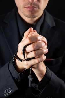 Christian person praying, low key image. hands of a man in black suit or a priest portraying a preach