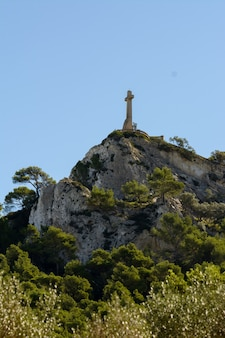 Christian religious sign on top of a mountain surrounded by pine forest