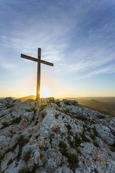 キリスト教のシンボル日の出の山の頂上に木製の十字架