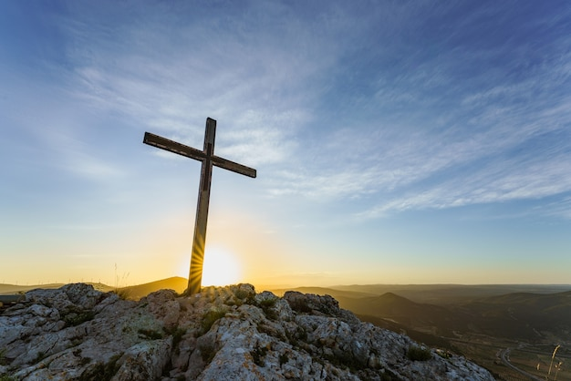 Christian symbol wooden cross on the top of a mountain at sunrise