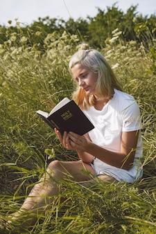 フィールドで聖書を読んでいるキリスト教の10代の少女。信仰、精神性、宗教の概念。