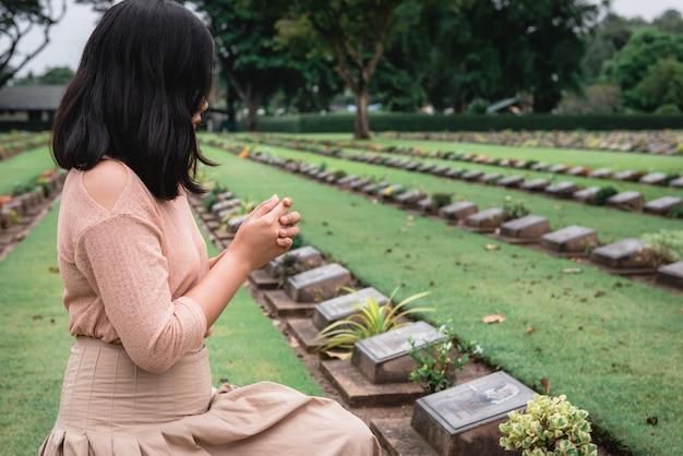 Женщина-христианка сцепила руки во время почитания и молитвы военным на военном кладбище.