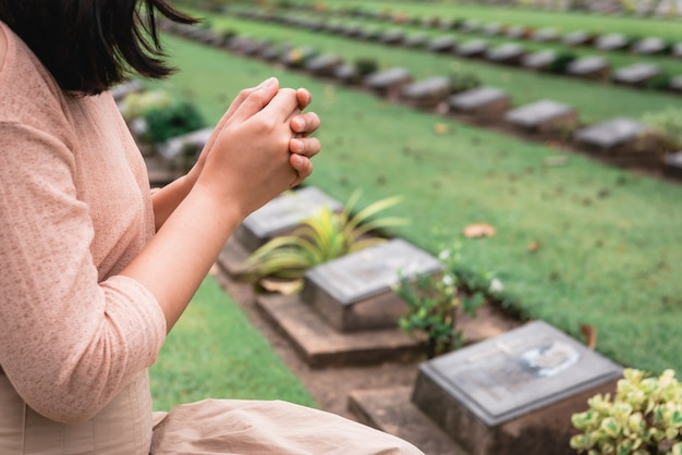 戦争の墓地で軍を称え、祈る間、クリスチャンの女性は握りしめられます。