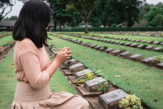 Christian woman hands clasped while honoring and praying to military in war cemetery.