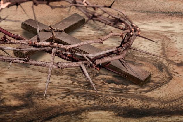 机の上のキリスト教の木製の十字架とイバラの冠
