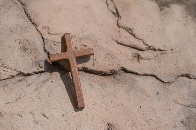 Christian wooden cross on the ground.