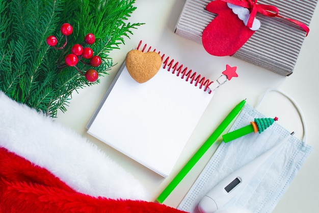 Christmas 2021 notebook to-do list or wish list, pen, natural decorations and medical mask and thermometer