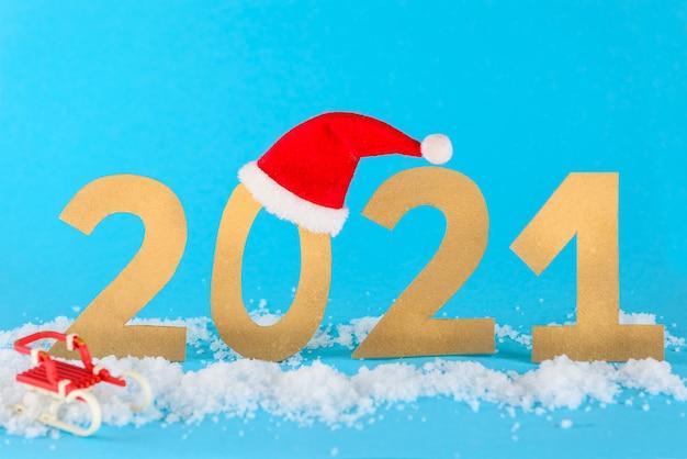 2021年のクリスマス、青い背景にそりと帽子で雪の中で数えます。
