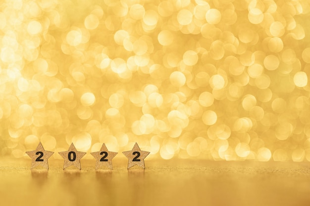 Christmas and 2022 new year abstract background with shiny gold glittered bokeh