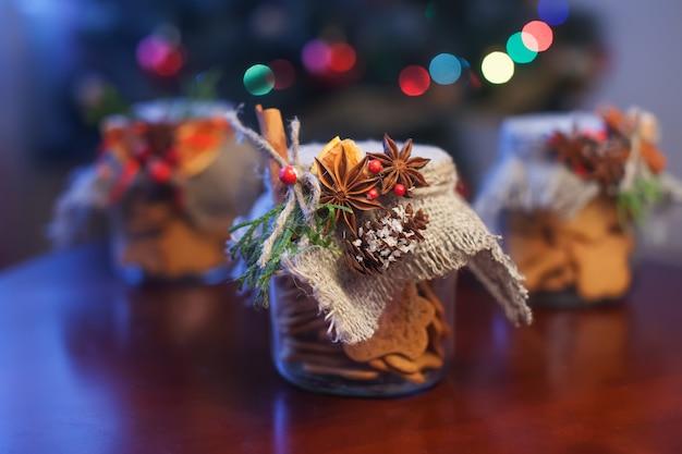 茶色のテーブルの上の瓶の中のクリスマスã'âookies。クリスマスのヒイラギ。お祭りの装飾