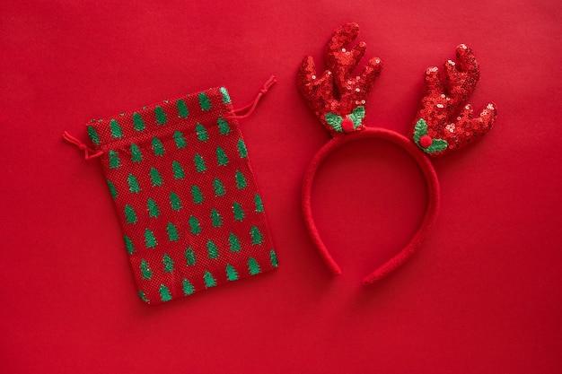크리스마스 액세서리, 빨간색 반짝이 표면에 사슴 뿔 머리띠 및 선물 가방