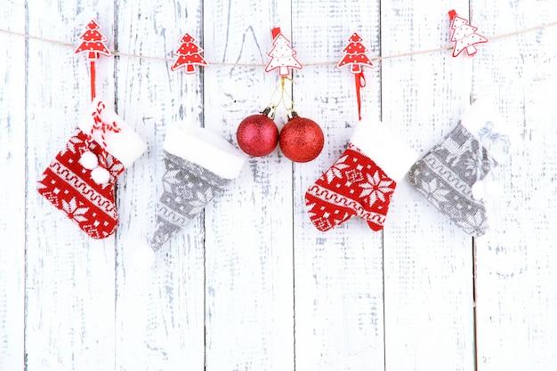 Рождественские аксессуары, висящие на белой деревянной стене