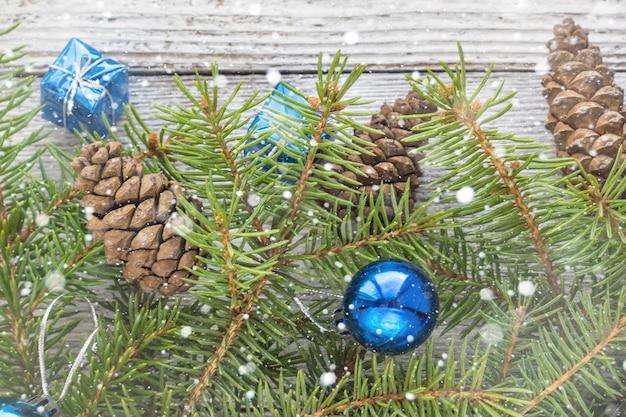 木製の白い背景の上の青、コーン、モミの枝のクリスマスアクセサリー