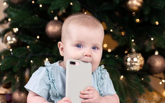 電話で話しているクリスマスの愛らしい小さな女の赤ちゃん。クリスマスツリーの背景に赤ちゃんの子供の肖像画。クリスマスかわいい幼児。