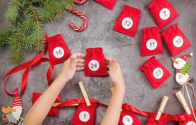 Christmas advent calendar on dark backgroundnext to the fir branches hands of girl holding a bag
