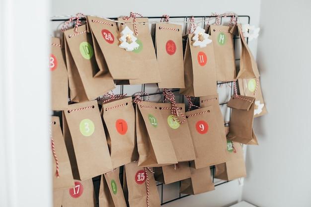 크리스마스 강림절 달력입니다. 아이들을 위한 선물이 든 에코 종이 가방. 지속 가능한 크리스마스.