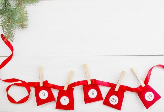 전나무 가지 옆에 흰색 나무 배경에 숫자가 있는 크리스마스 출현 달력