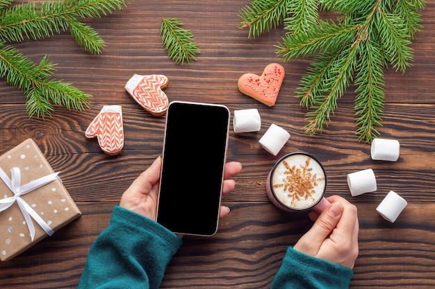Рождественская атмосфера с макетом смартфона в женской руке на деревянном столе с еловыми ветками и сладостями. новогодняя концепция покупок в интернете.