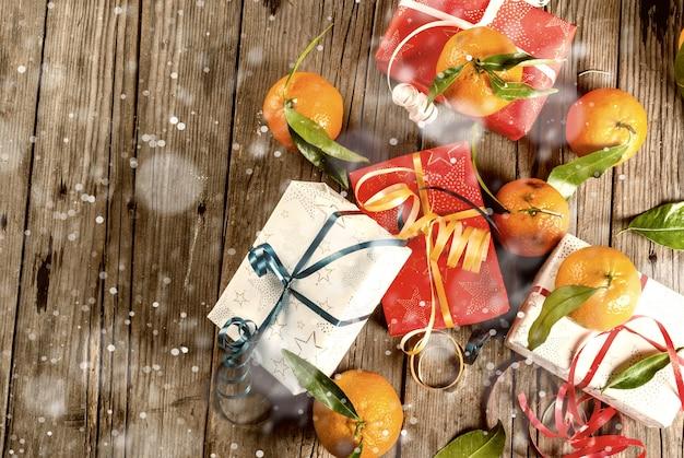 Рождество и свежие мандарины с зелеными листьями в белой корзине, рождественские украшения и подарочные коробки, на старом деревенском деревянном столе, тонированное эффект снега вид сверху