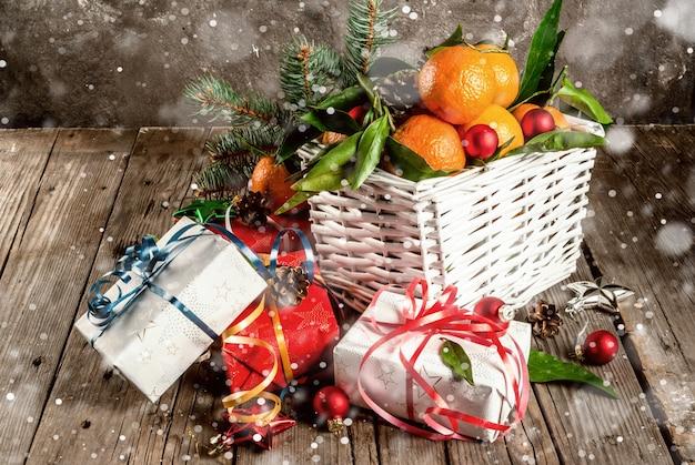 크리스마스와. 흰색 바구니, 크리스마스 장식 및 선물 상자에 녹색 잎을 가진 신선한 귤, 눈 효과와 톤의 오래 된 소박한 나무 테이블에