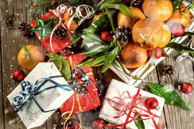 Рождество и свежие мандарины с зелеными листьями в белой корзине, рождественские украшения и подарочные коробки, на старом деревенском деревянном столе, вид сверху в тонусе, эффект снега