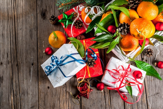 Рождество и свежие мандарины с зелеными листьями в белой корзине, рождественские украшения и подарочные коробки, на старом деревенском деревянном столе, вид сверху