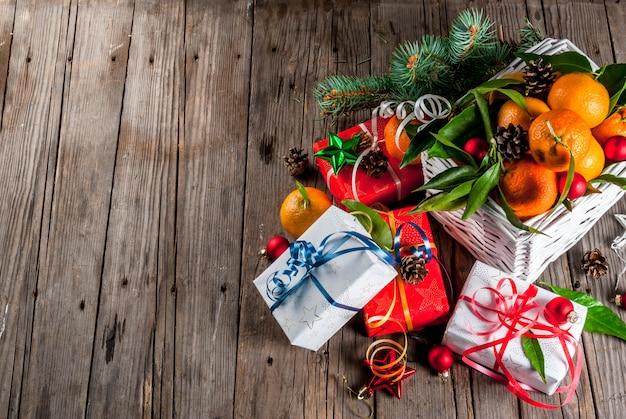 크리스마스와. 오래 된 시골 풍 나무 테이블에 흰색 바구니, 크리스마스 장식 및 선물 상자에 녹색 잎을 가진 신선한 귤