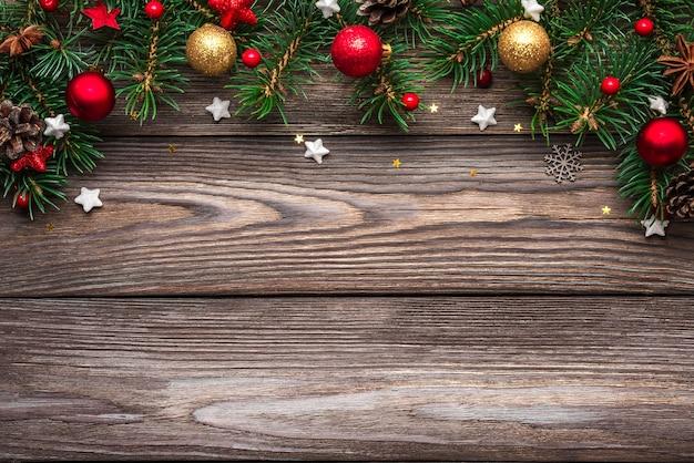 Рождество и счастливый новый год фон. еловые ветки и праздничные украшения на деревянном столе