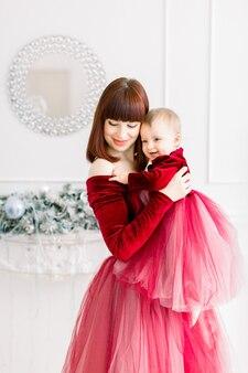 크리스마스와 새해 휴일. 엄마가 그녀의 귀여운 아기 소녀를 안고