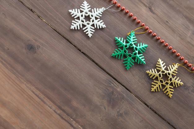 クリスマスとホリデーシーズンのコンセプト。コピースペースを持つ古い木の板のクリスマス雪フレーク飾りと赤いビーズアクセサリーの平面図です。