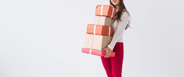 クリスマスと休日のコンセプト – コピースペースのある白い背景にギフトボックスのスタックを保持している女性の接写