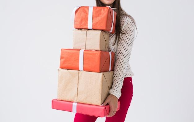 クリスマスと休日のコンセプト – 白い背景に多くの贈り物を持つ女性の接写