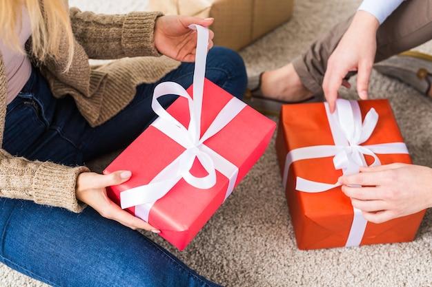 クリスマスと休日のコンセプト-自宅で贈り物を開く若い幸せなカップルのクローズアップ、上面図
