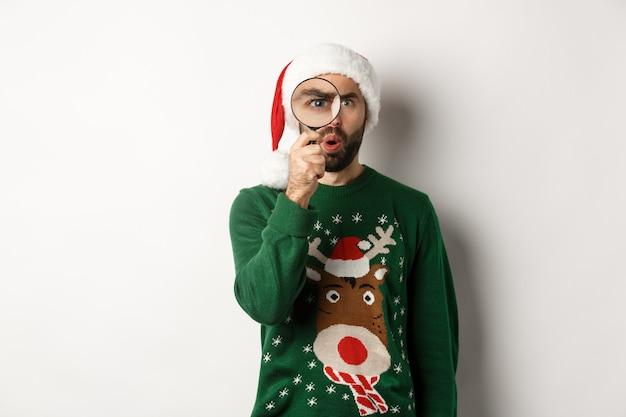 크리스마스와 휴일 개념입니다. 돋보기를 통해 무언가를 보고 있는 호기심 많은 남자, 크리스마스 스웨터를 입은 산타 모자에 서서 흰색 배경 위에 서 있는