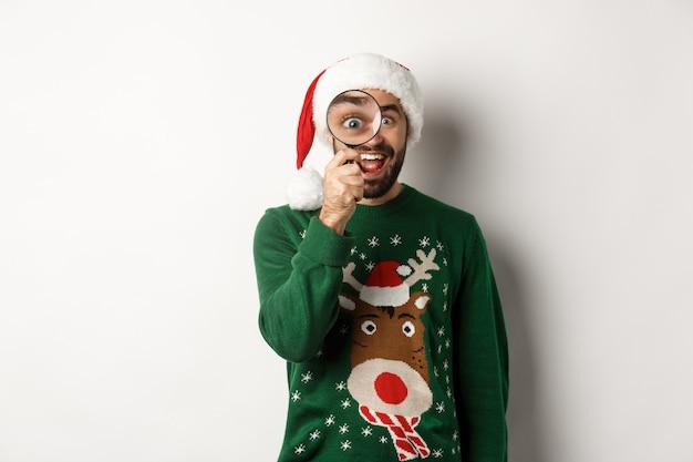 크리스마스와 휴일 개념입니다. 산타 모자를 쓴 재미있는 수염 난 남자가 돋보기를 통해 놀랍게도 흰색 배경 위에 서 있는 것을 발견했습니다.