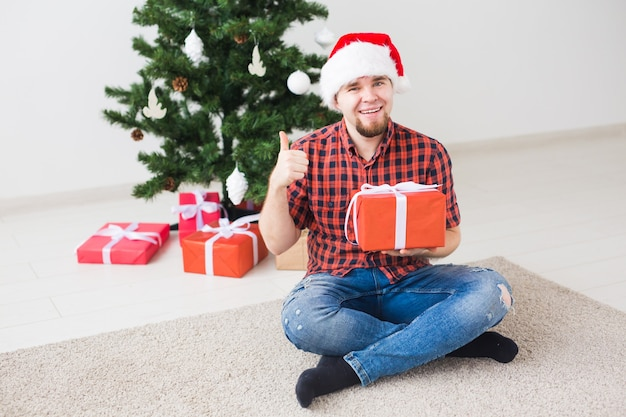 Концепция рождества и праздников - забавный человек в шляпе санта держит подарок дома в гостиной.